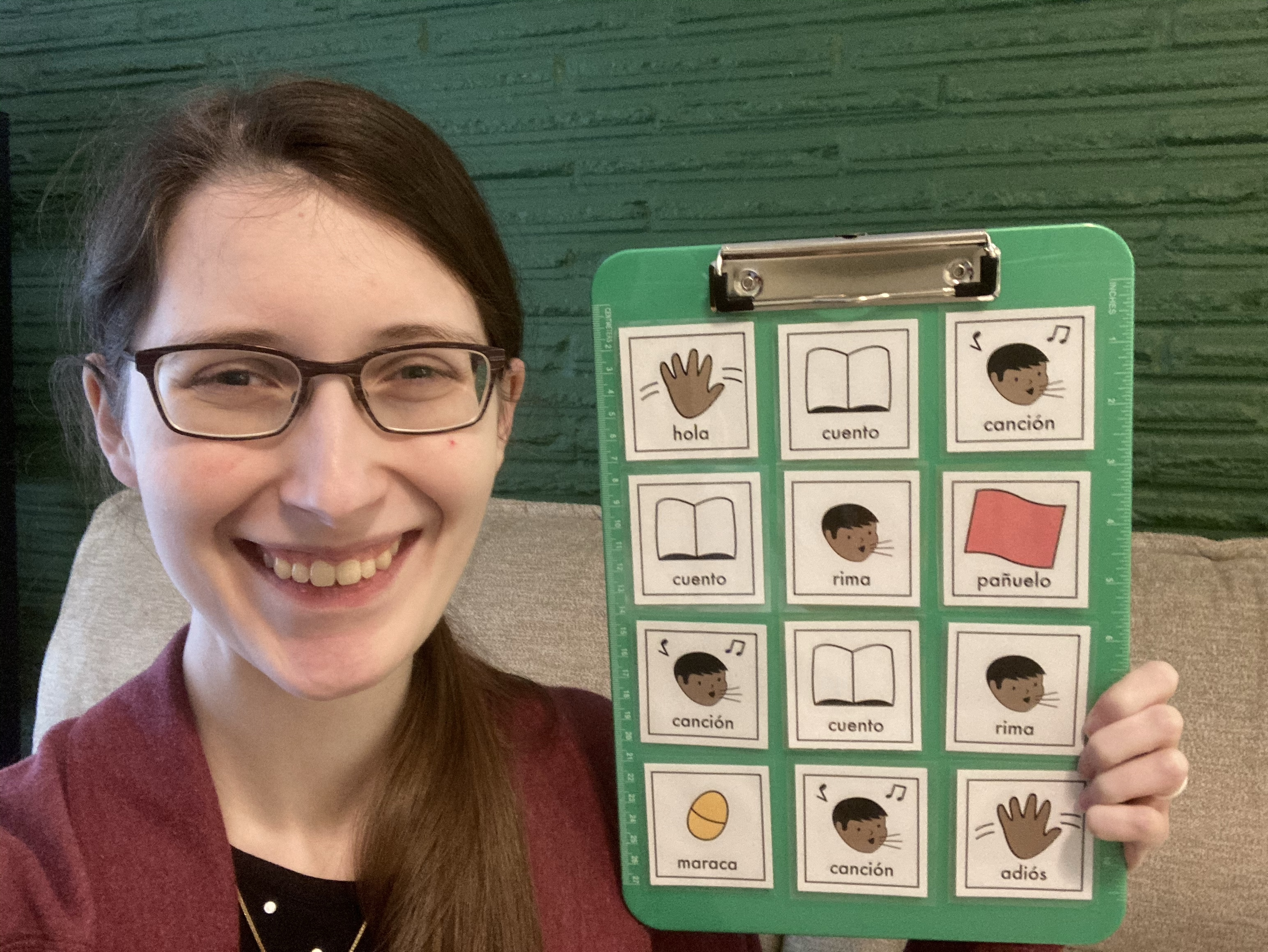 Photo of a women holding a clipboard with visual storytime schedule icons for hola, cuento, canción, rima, pañuelo, maraca, and adiós.